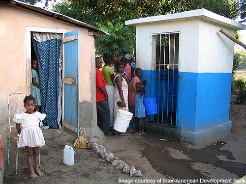 People gather to collect water from a water kiosk.