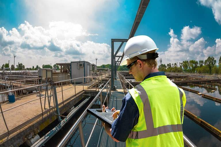 worker using tablet at water processing plant